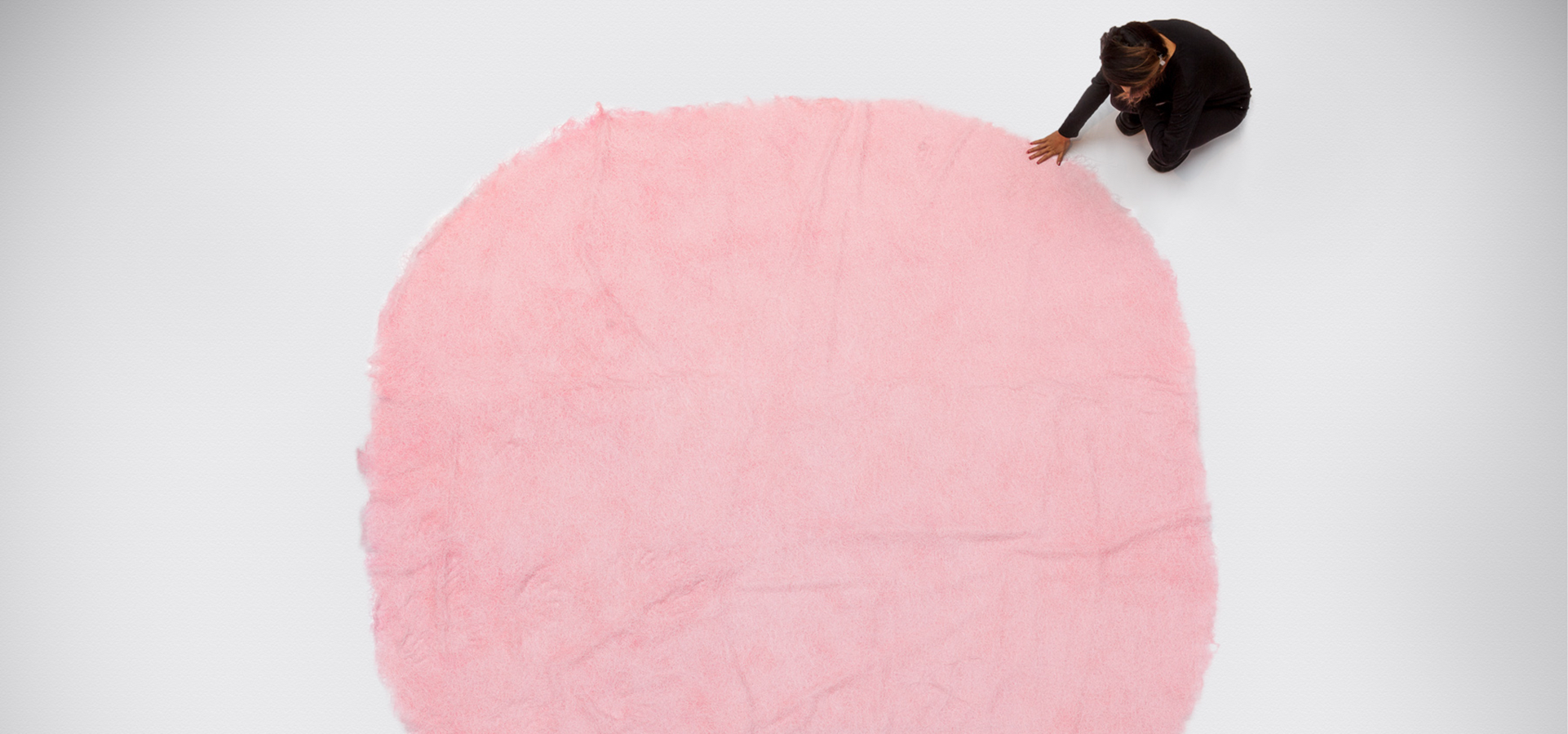 Overhead of a person touching a round pink knitted thread installation