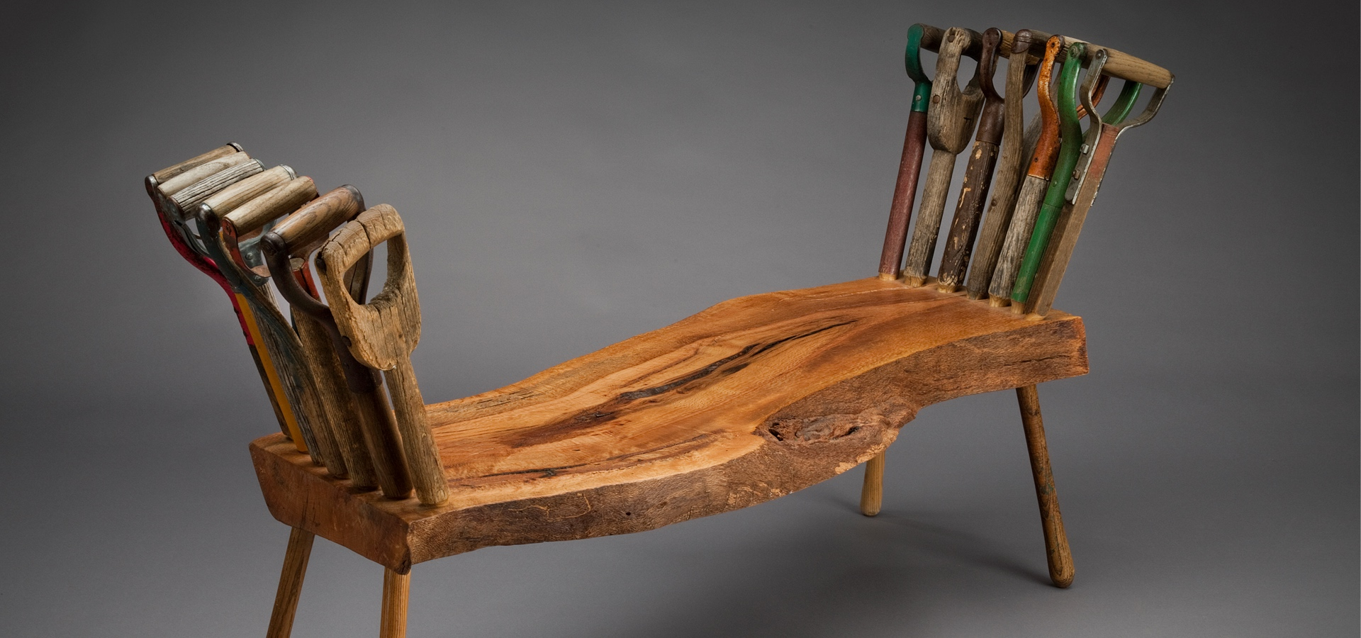 Wood bench with tool handles as decorative supports on either side