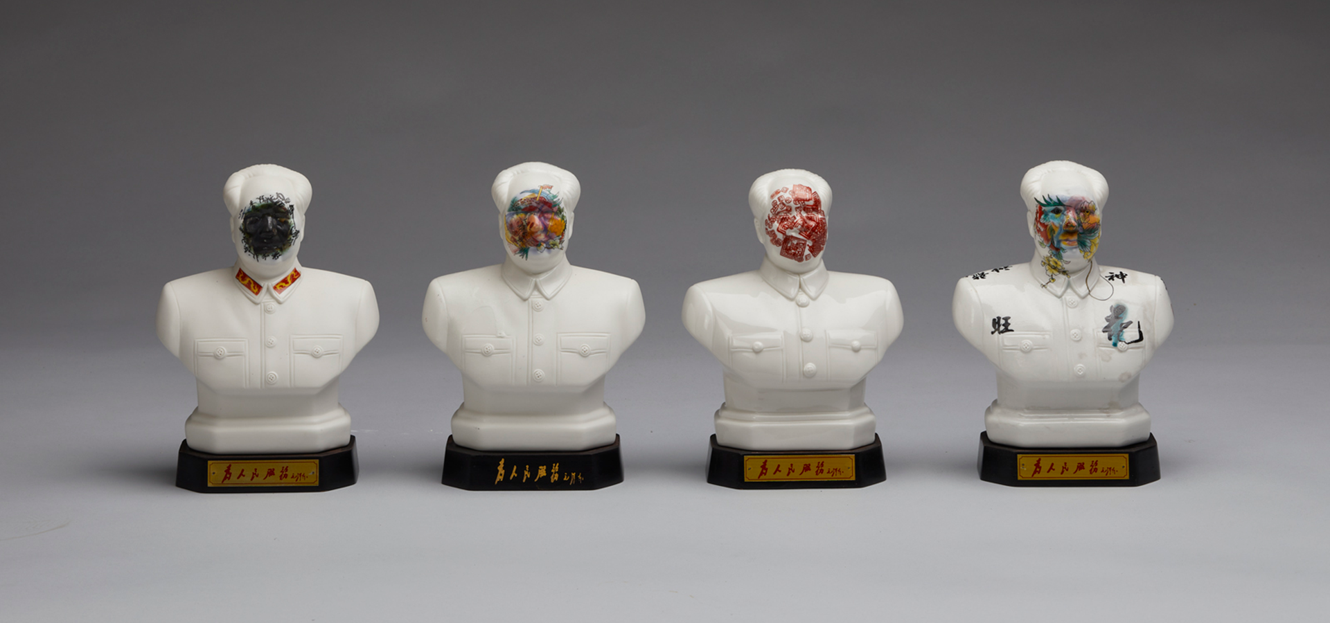 Four ceramic busts of Mao Zedong with paint covering their faces