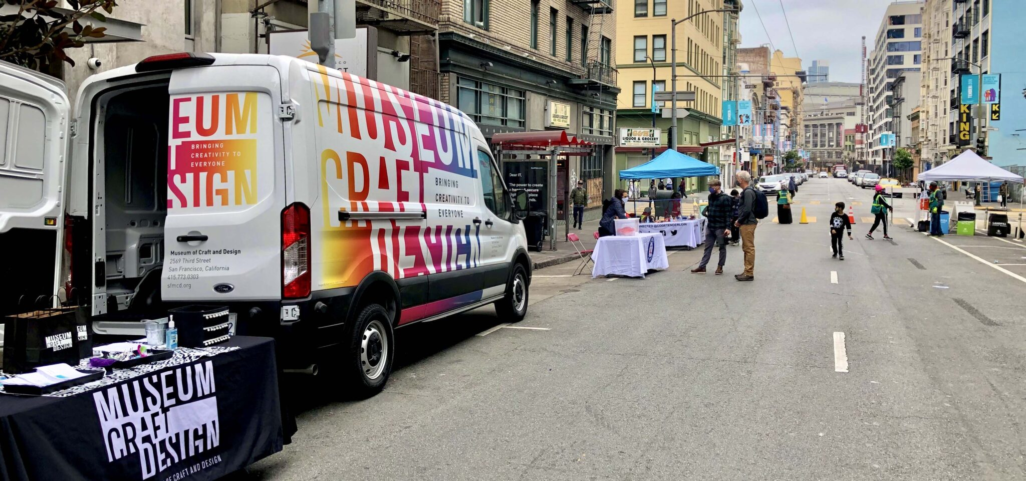 MakeArt van and table set up in street with people walking around